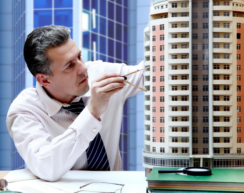 Архитектор работает с макетом высотного дома