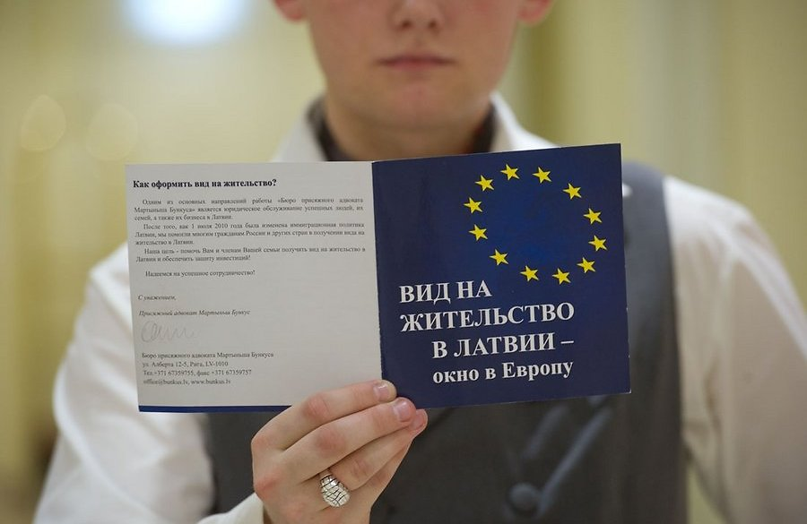 Мальчик с буклетом о ВНЖ Латвии