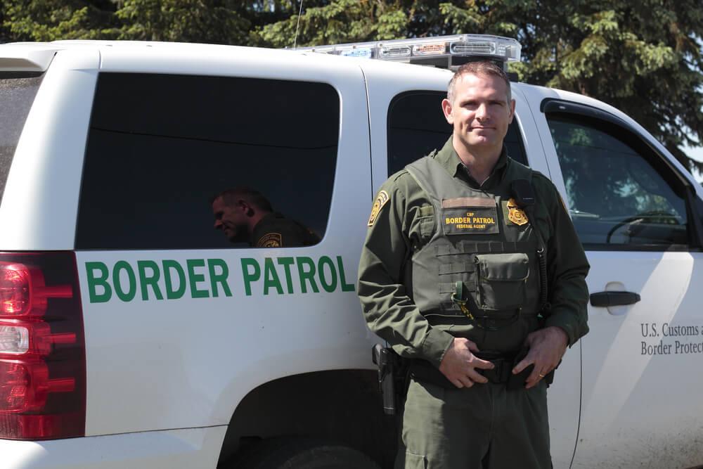 Американский полицейский из службы пограничного контроля на фоне патрульной машины