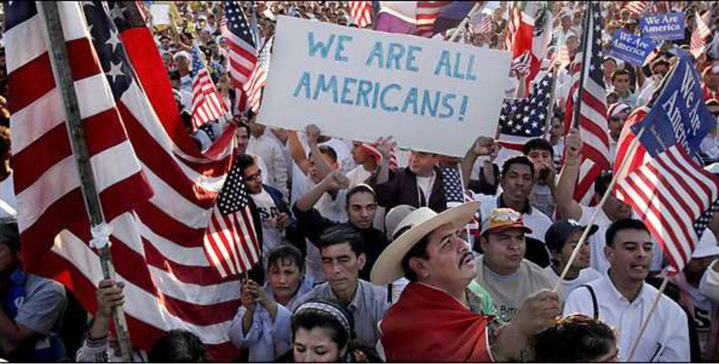 Демонстранты латиноамериканской внешности несут плакат и американские флаги