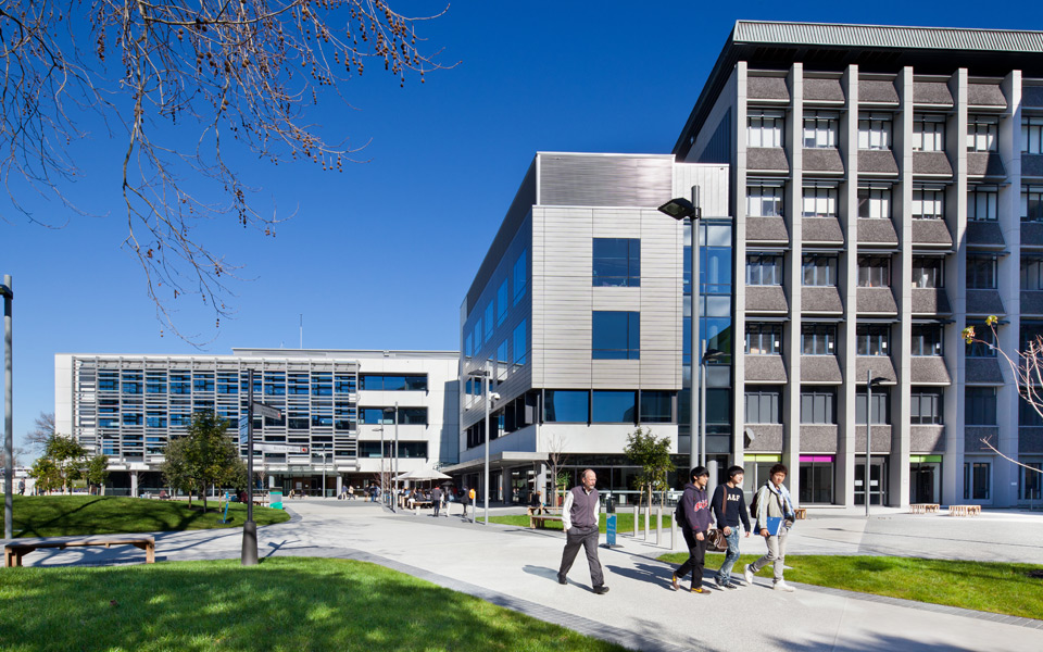 Студенты из Азии идут на фоне университета в Окленде