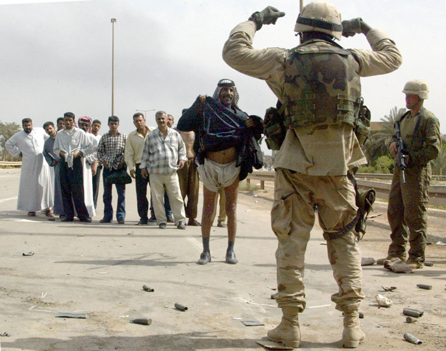 Американский солдат проверяет месногот жителя на отсутствие оружия и взрывчатки