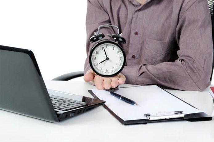 Человек за ноутбуком с будильником на ладони