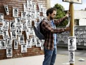 Мужчина расклеивает листовки с объявлениями