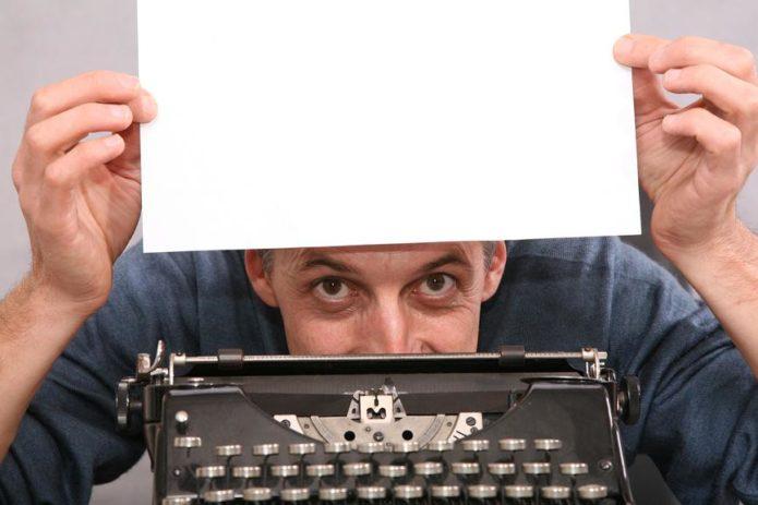 Мужчина у печатной машинки с белым листом в руках