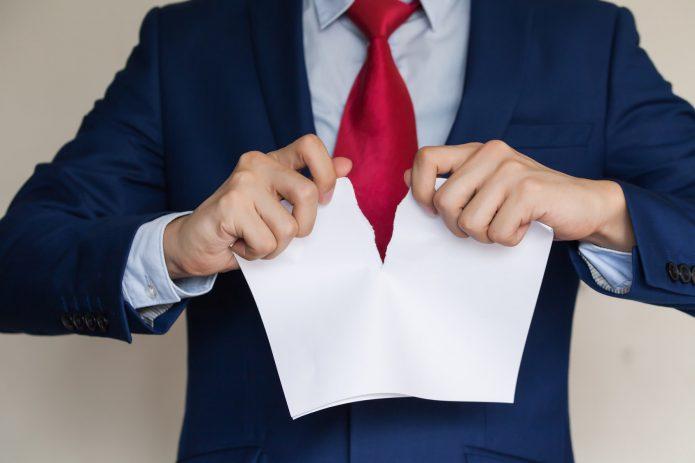 Мужчина рвёт бумагу