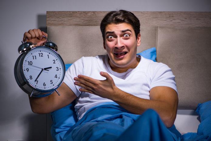 Мужчина в кровати с будильником в руках