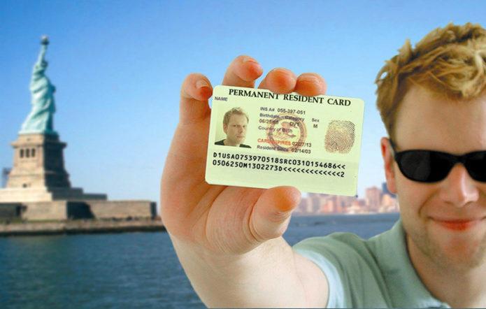 Мужчина держит в руке грин-карту