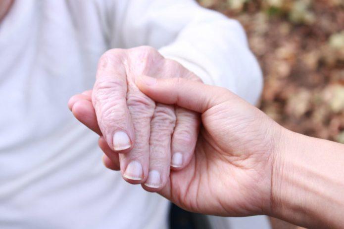 Сын держит руку пожилого родителя