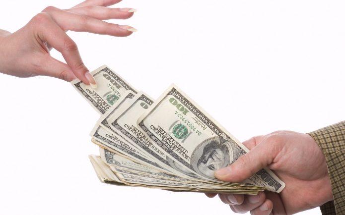 Рука вытаскивает доллар из пачки с купюрами